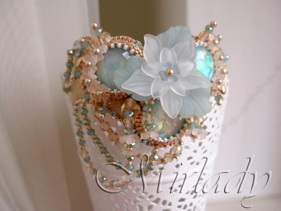 A romantic V-shaped bracelet made with Swarovski® beads, Czech glass beads and resin cabochons in shades of sand and aqua.